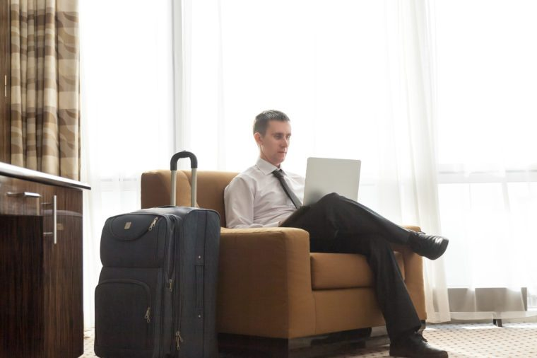 Portrait of handsome young business man wearing formal white shirt and black tie sitting in armchair in hotel room with packed luggage bag on the floor. Traveller working on laptop