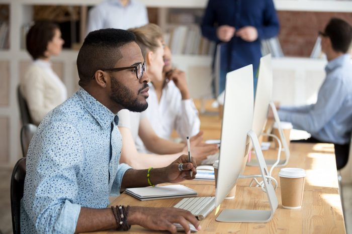 Focused african employee wearing glasses looking at computer screen sitting in shared office. Serious black manager holding pen make some notes on textbook using pc working on project analyzing data