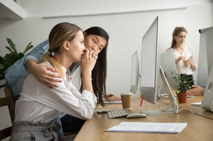 Asian colleague embracing supporting caucasian woman reading bad news in email, teammate comforting stressed frustrated female coworker upset by dismissal, helping to solve problem online in office
