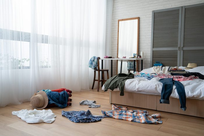 straw hat and colorful clothes in luggage on wooden floor. empty nobody in messy white bed in bedroom packing suitcase for travel abroad summer vacation holidays. mirror by window at dressing table.