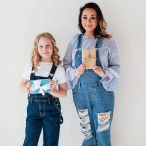Mom and daughter in jeans hold gifts for the holiday
