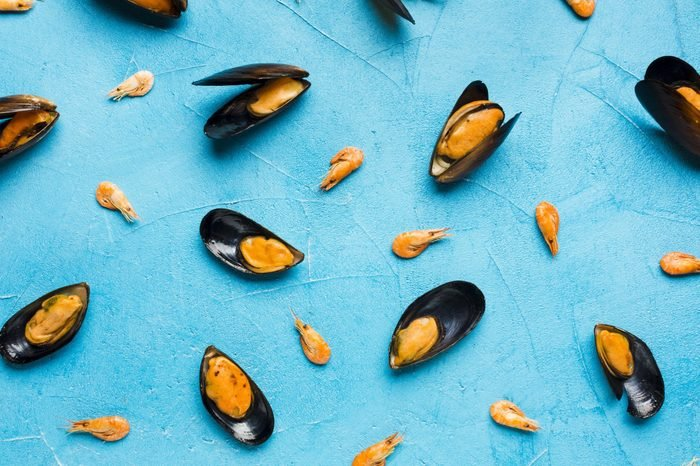Flat-lay boiled mussels scattered on tabletop
