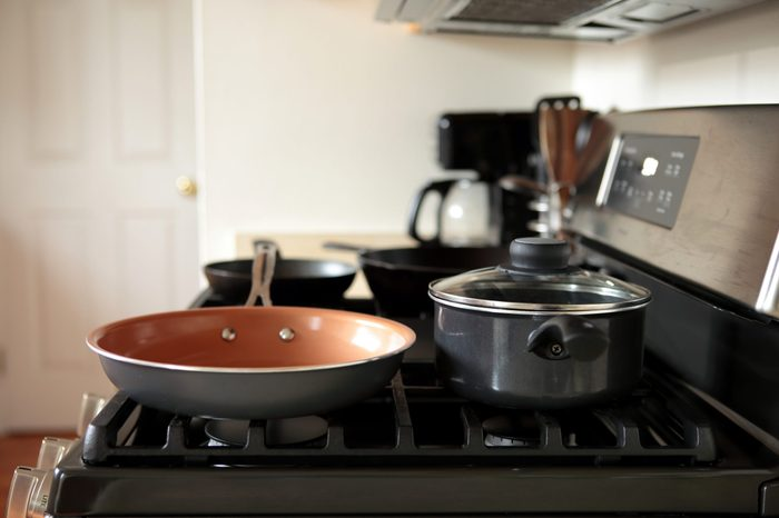 Modern stainless steel gas stove oven in a home with various cookware.