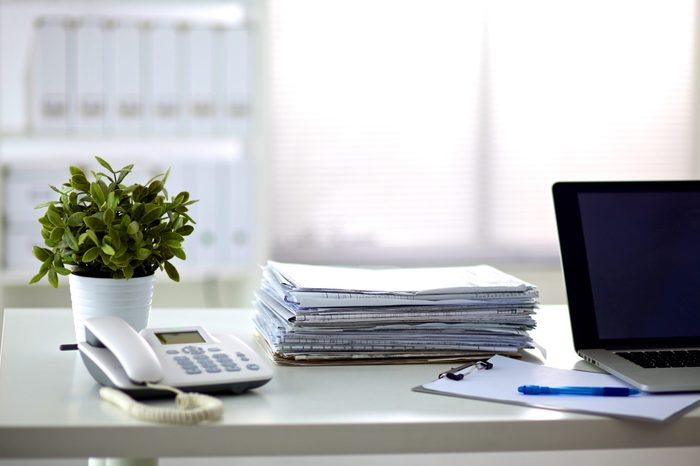 a stack of papers on the desk with a computer