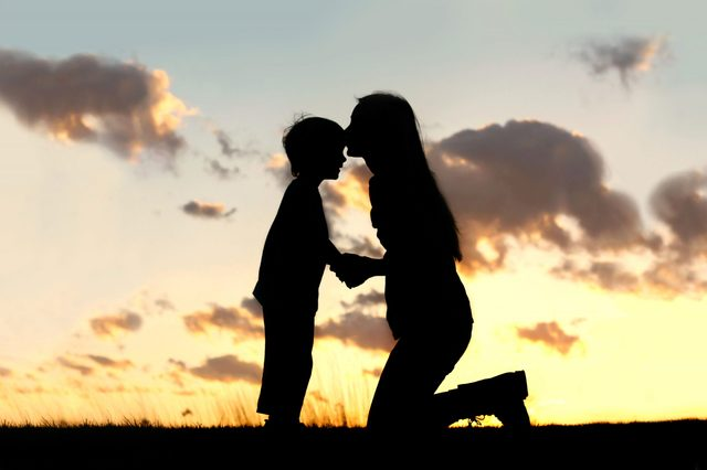 Silhouette of a young mother lovingly kissing her little child on the forehead, outside isolated in front of a sunset in the sky on a summer day.