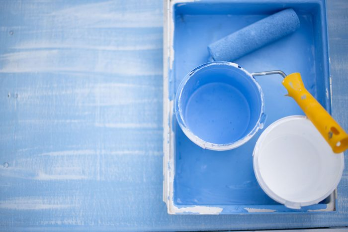 The roller for coloring lies in the tray with blue and white paint