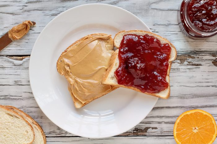 Top view of open face homemade peanut butter and strawberry Jelly sandwich on oat bread, over a white rustic wooden table / background. Served with fresh oranges / fruit.