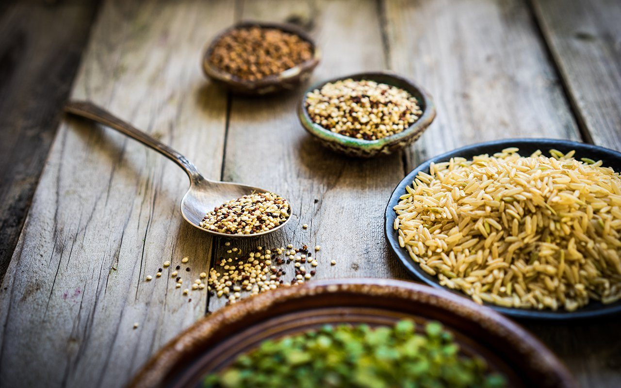 Peas, brown rice, quinoa and buckwheat on wooden background