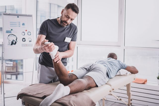 Muscle relaxation. Relaxed sportsman looking at window while visiting rehabilitation massage