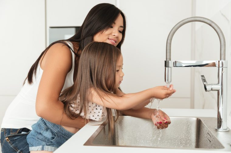 Young asian mother helping her daughter to wash hands in a sink on a kitchen