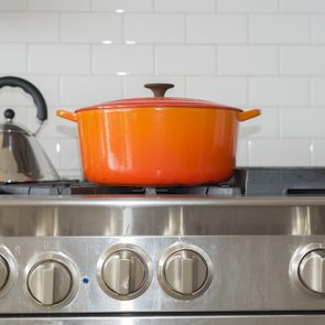 Bright orange pot on top of upscale home stove
