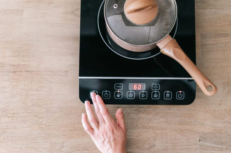 Cropped view of hand young adult woman choose or switch program at small electric stove with control panel and pan on top. Kitchen room with wooden surface on table