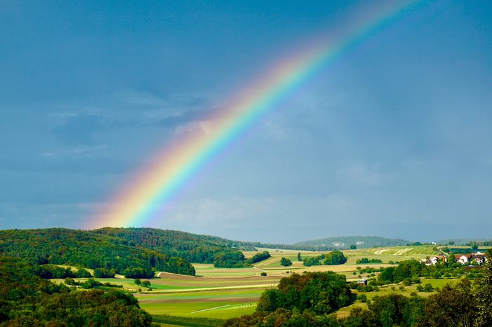 Rainbow in a rural area in Switzerland beautiful intense rainbow colors wit very special light effects from the sun through the clouds
