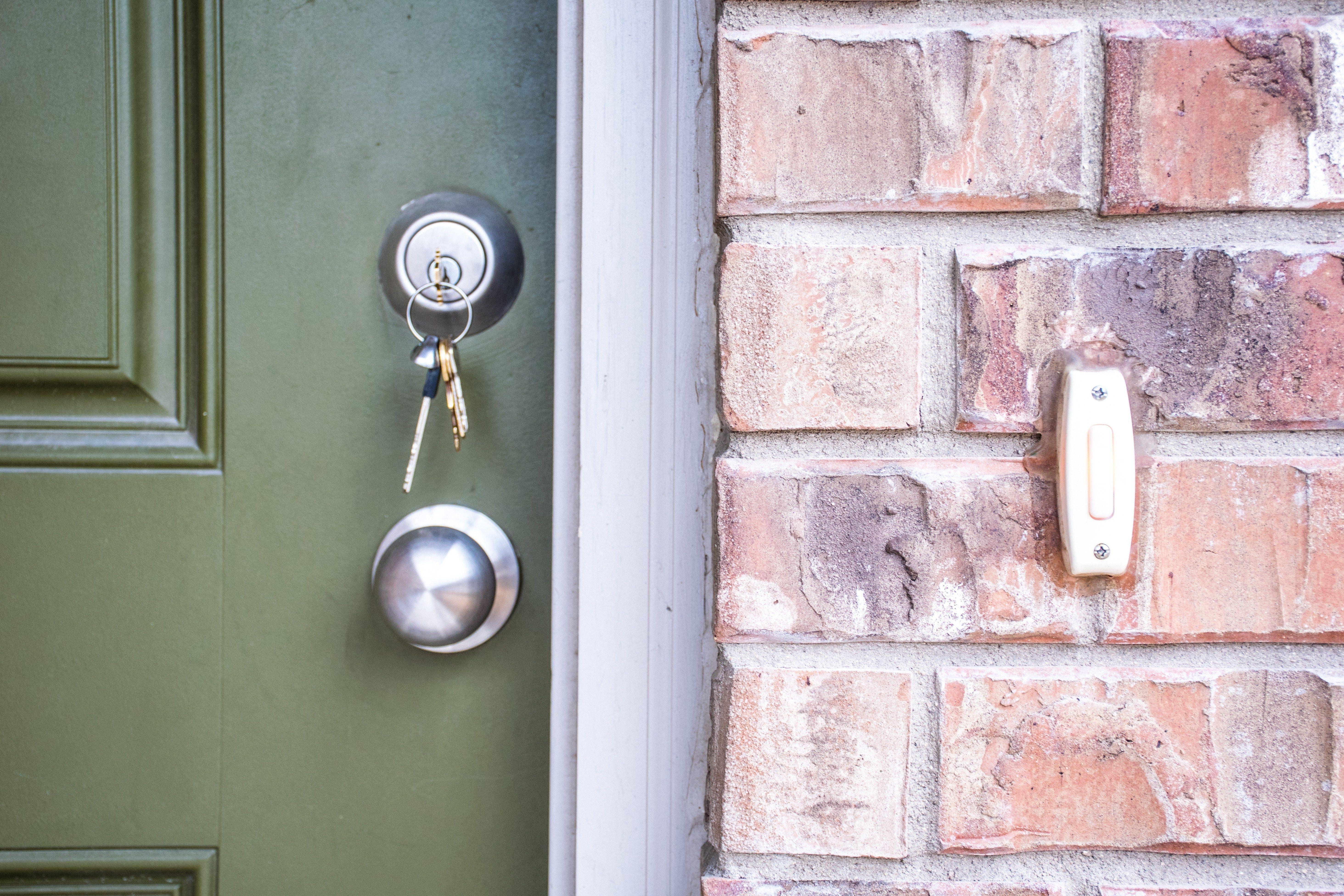 Keys inside front door Deadbolt of new Brick Home. Door bell and green front door.