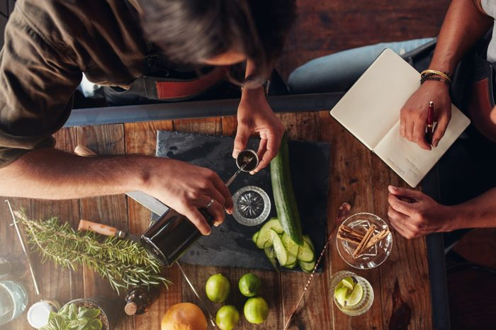 Two barmen creating new cocktail recipe and taking down notes. Top view of man pouring mixture into a jigger to prepare a cocktail and another taking down notes.
