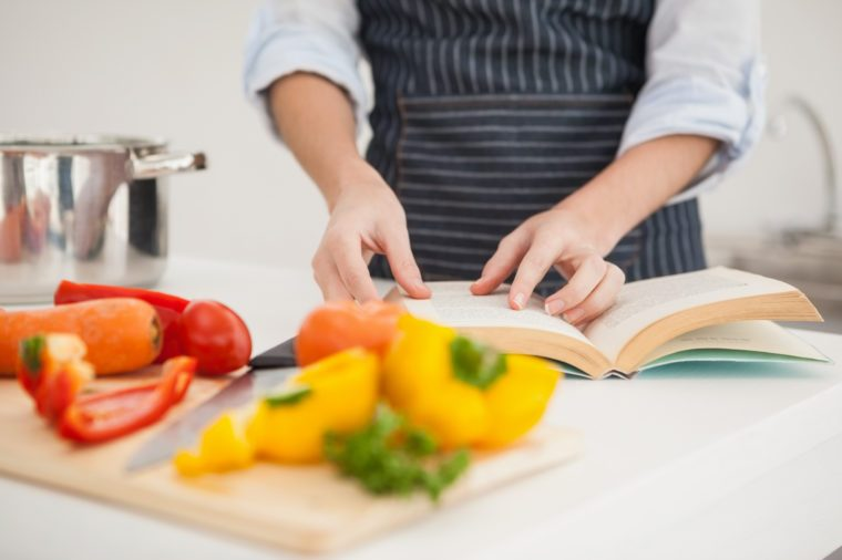 Woman following a recipe in book at home in the kitchen
