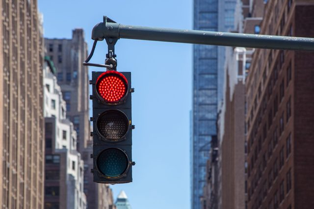 Traffic light closeup with red signal. Traffic light on the background of skyscrapers in New York. Red color traffic light with buildings in the background. Traffic light wallpaper.