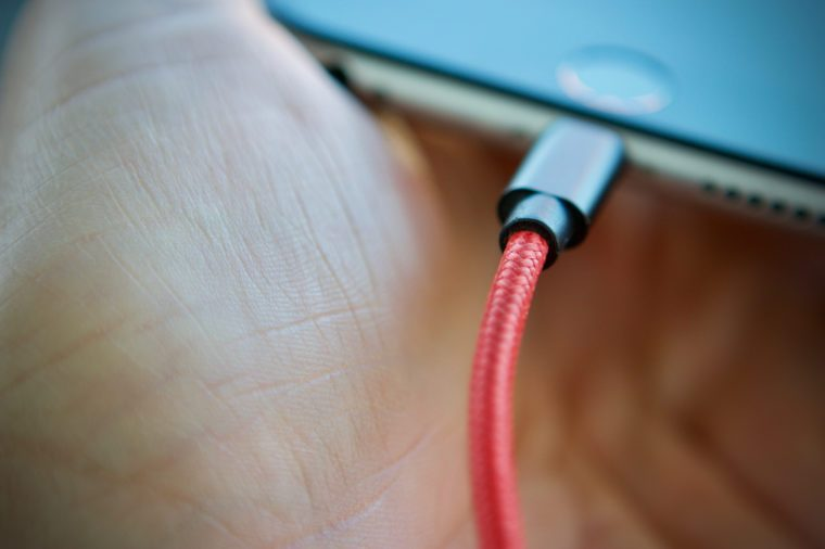 red charging lead plugged into a smartphone held in mans hand