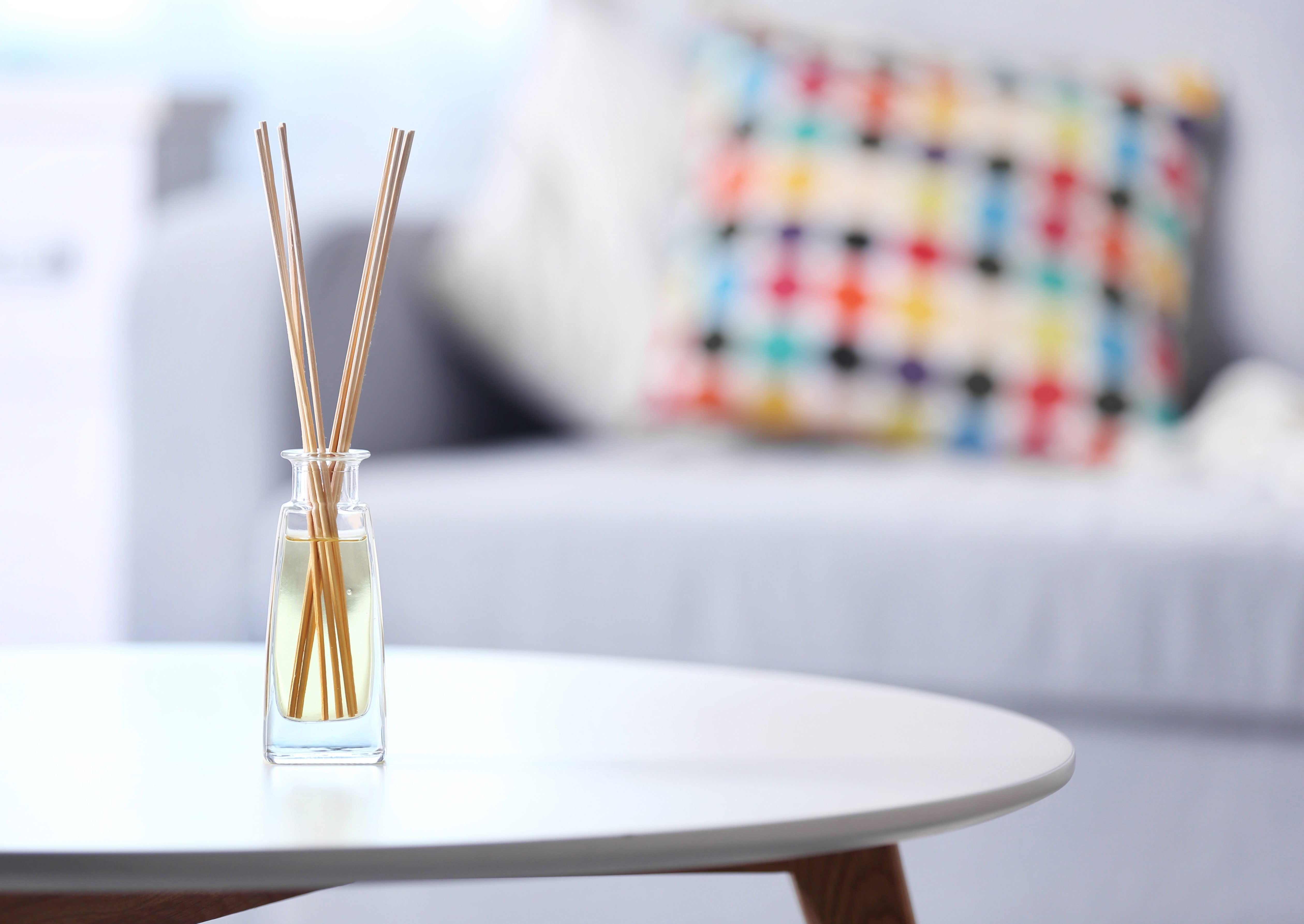 Handmade reed freshener on white table in living room, close up