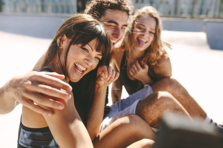 Group of friends posing for a selfie outdoors. Smiling woman taking a selfies while hanging out with friends outdoors.