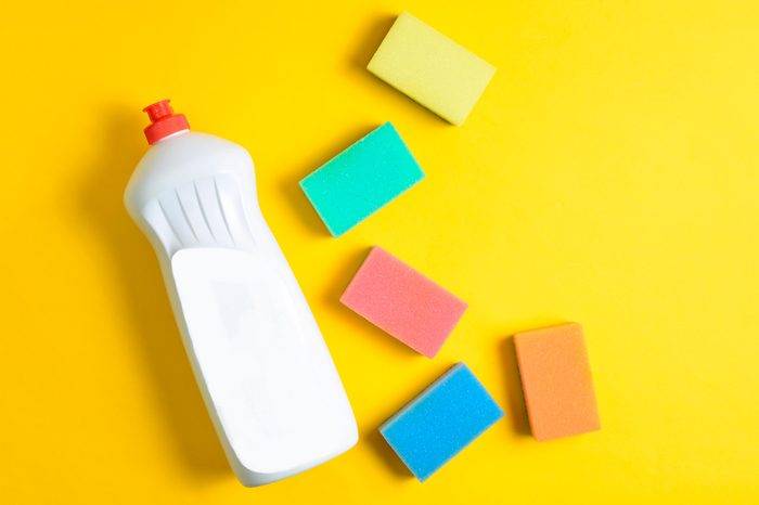 Plastic bottle of dishwashing detergent, sponges on yellow pastel background, top view, flat lay, minimalism