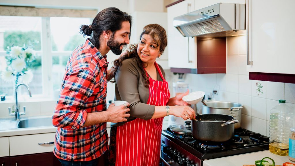 Mature woman is cooking in her kitchen and her son is looking over her shoulder to see what she is making
