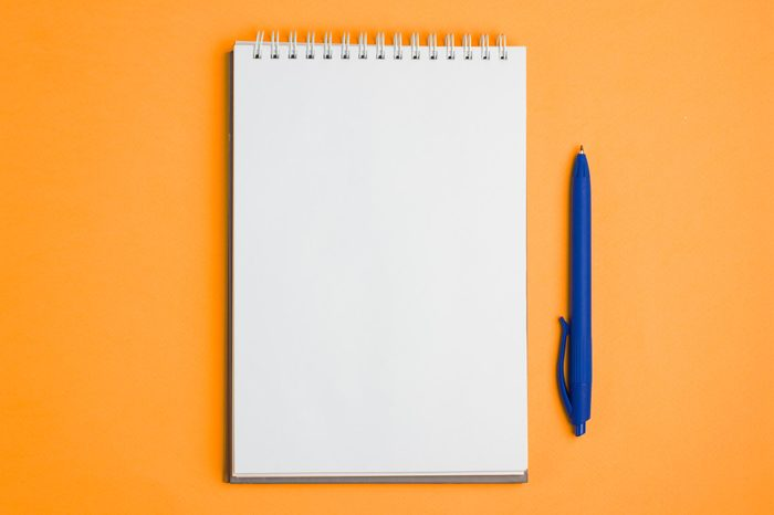 Blank notebook with pen on yellow pastel background. Flat lay concept. Copy space