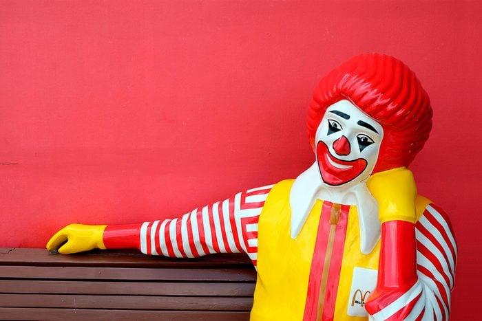 ronald mcdonald statue sitting on a bench at mcdonalds