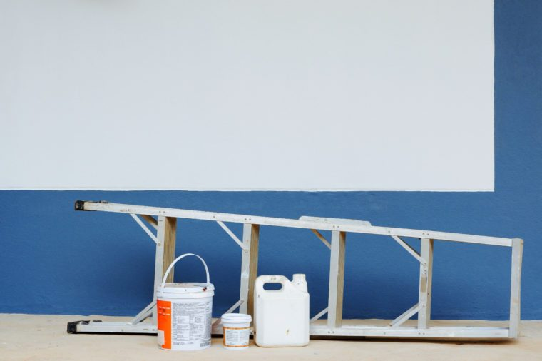 Aluminum ladder and paint accessories Near a wall painted successfully.