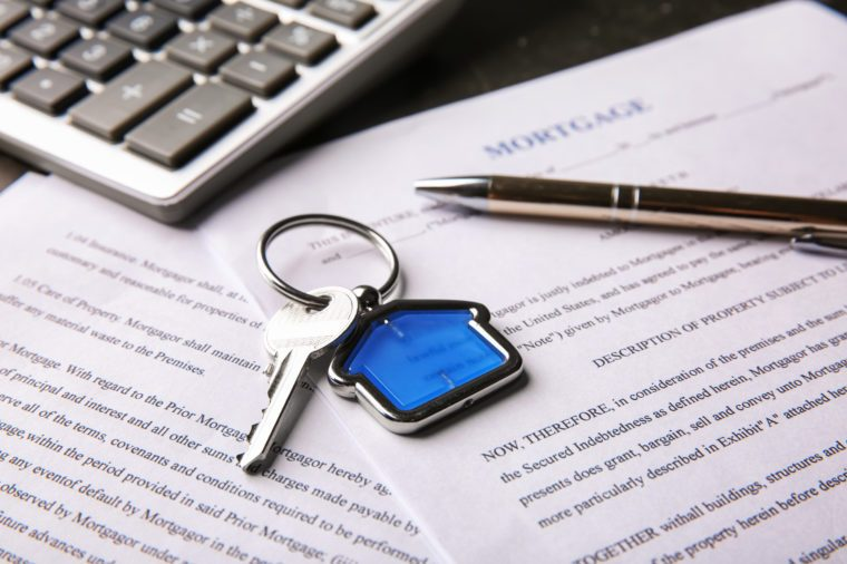 Key with trinket, pen and calculator on mortgage contract