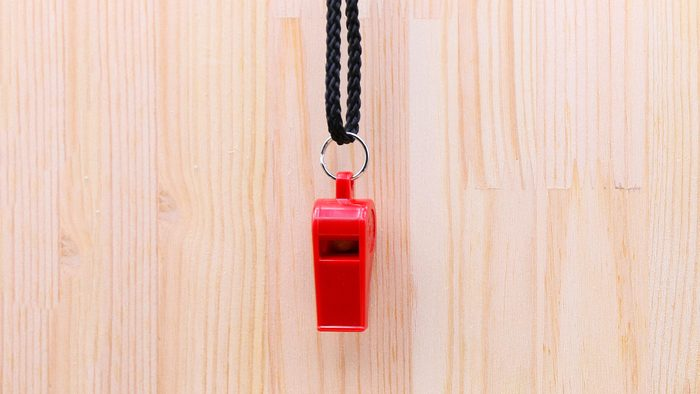 Red plastic Whistle on brown wooden background in sport object concept. Whistleblower concept.