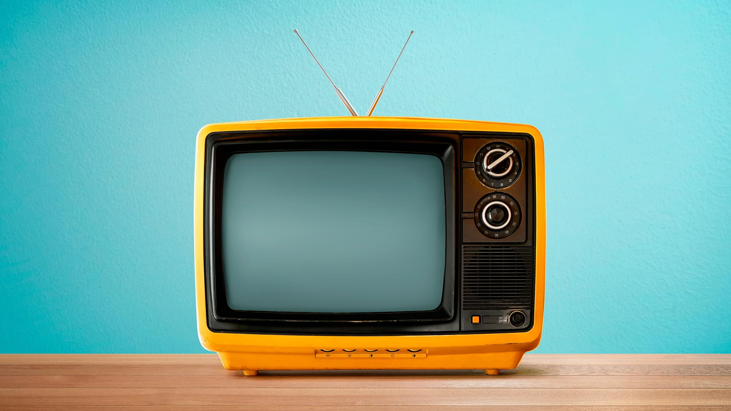 Yellow Orange color old vintage retro Television on wood table with mint blue background