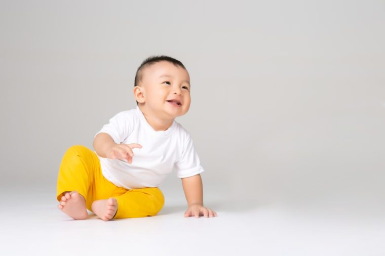funny baby boy sitting on white background