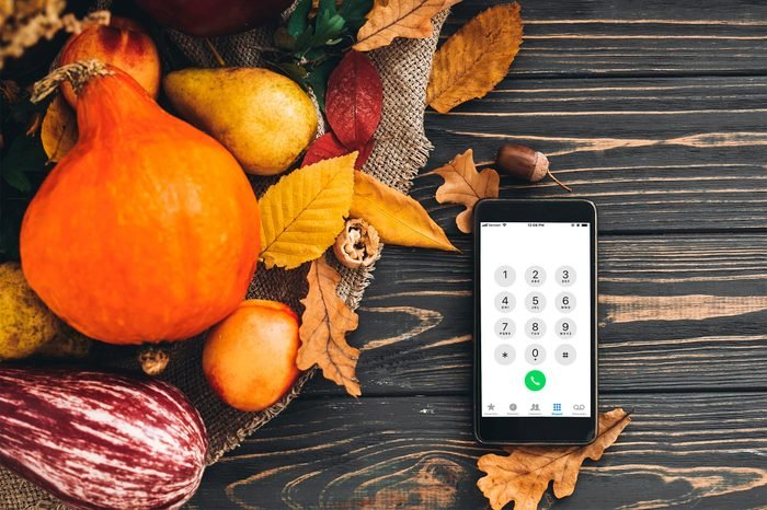 Happy Thanksgiving concept. Phone with dial screen and beautiful Pumpkin with bright autumn leaves, acorns, nuts, berries on wooden rustic table, flat lay.