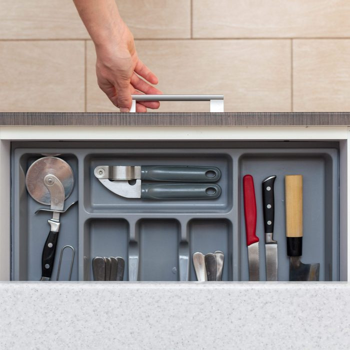 High angle top view photo of woman hand open kitchen drawer by door handle, with different cutlery spoon, pizza knife, fork and stuff