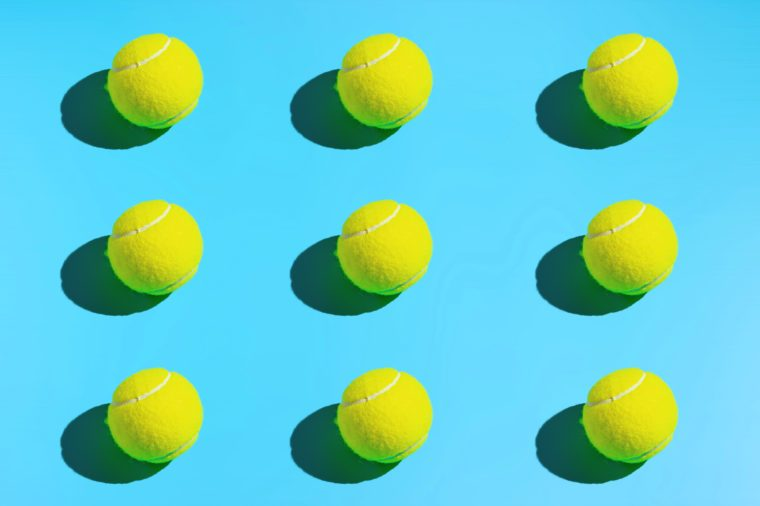 Symmetrical tennis balls on a blue background. Sports background.