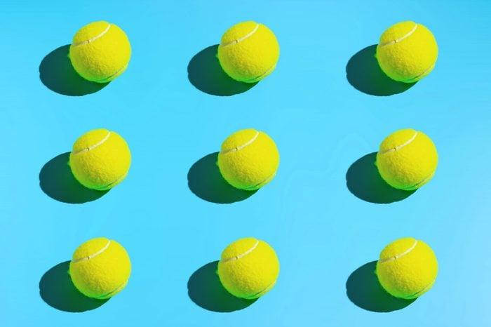 Symmetrical tennis balls on a blue background. Sports background.