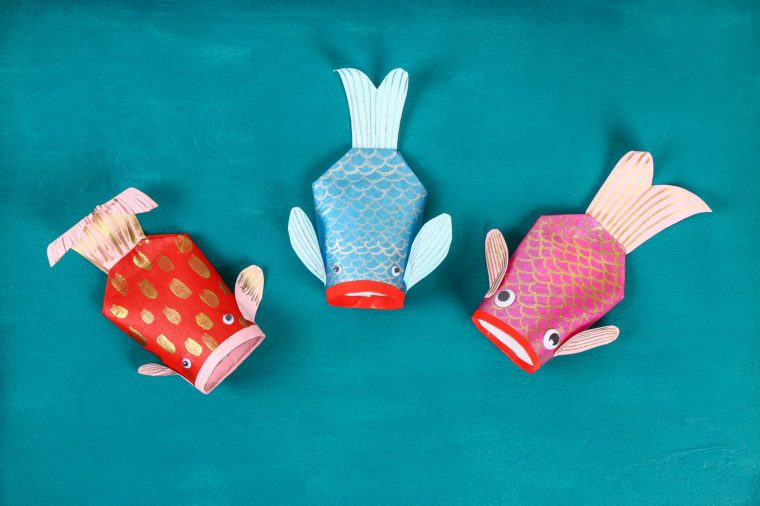 Diy koi carp fish on blue green background. Gift ideas, decor for the Chinese new year. Kid handmade. Carp koi fish of paper, toilet roll, googly eyes. Step by step. Process children crafts. Top view.