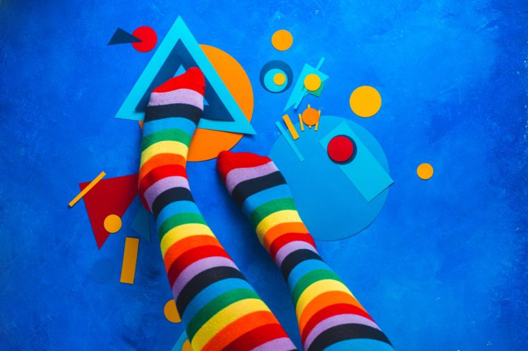 Girl legs in rainbow striped socks on a colorful background with color blocking simple shapes. Abstract geometry flat lay