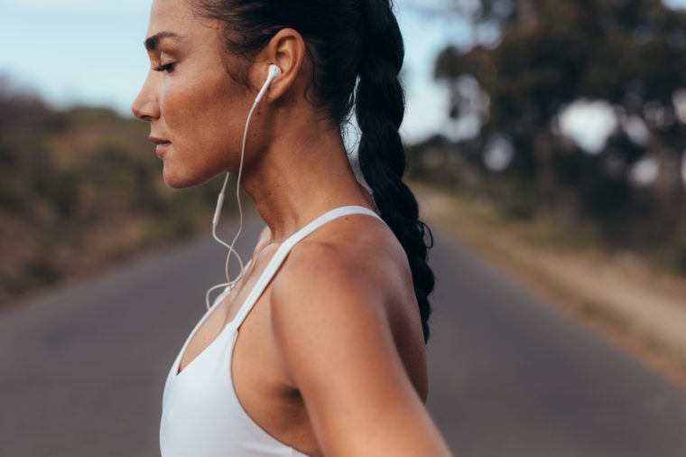 Side view of a female runner standing on a road in morning. Woman in fitness gear standing on a road listening to music using earphones.