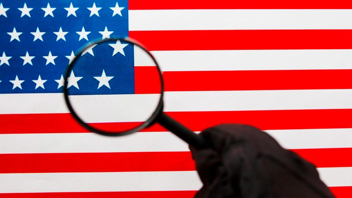US flag looking through a magnifying glass. Study of the history and culture of the country of the United States. The concept of studying geography, English and customs.