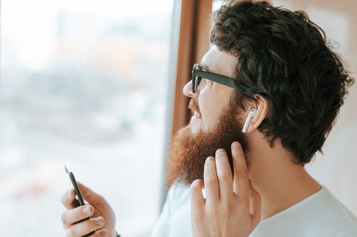 Handsome bearded businessman is using mobile and airpods, while talking with coworker near window