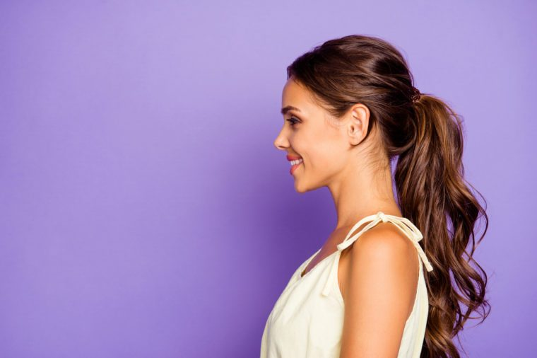 Close-up profile side view portrait of nice adorable well-groomed attractive stunning lovable fascinating magnificent winsome content cheerful cheery wavy-haired girl isolated over violet background