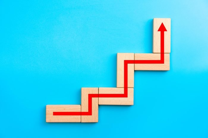 Wooden blocks stacking as step stair with red arrow up, blue background, Business growth success process concept, copy space