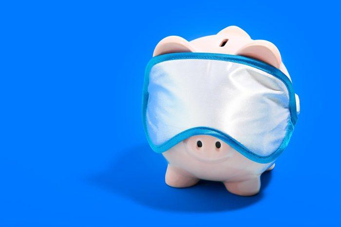 Piggybank with sleeping mask on blue background. Minimalism concept