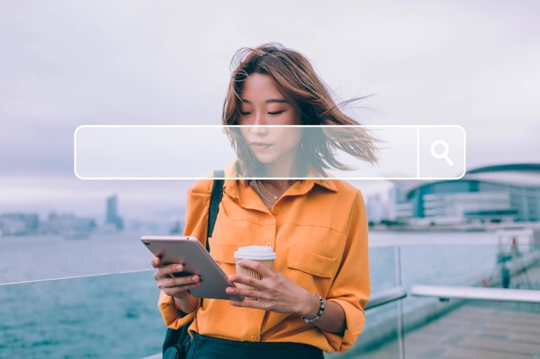 Beautiful Japanese hipster student checking received notification on modern touch pad standing at urban setting and using public internet connection for installation, millennial woman testing app