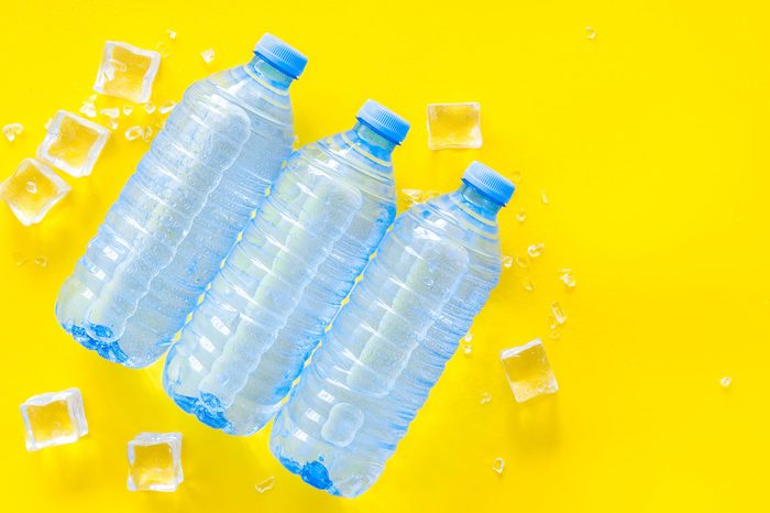 Plastic bottles with pure water and ice on yellow background top view space for text