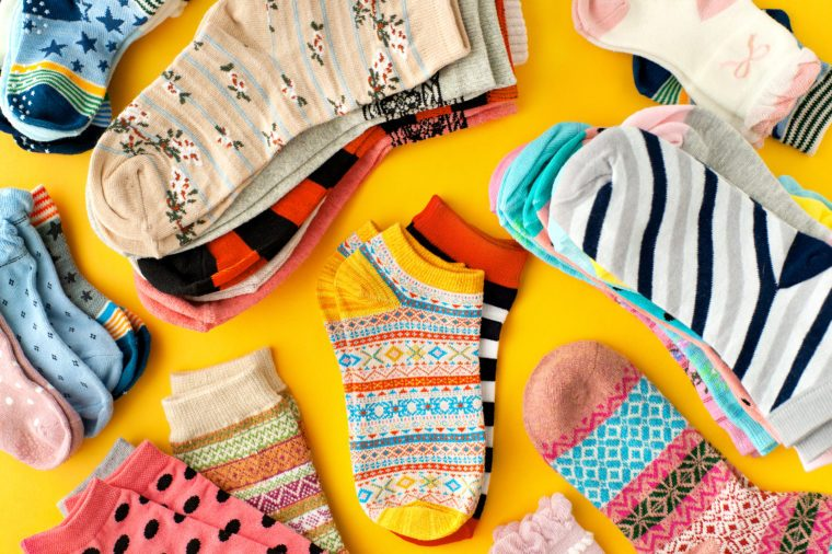 Lots of socks on a yellow background. Colorful socks scattered on a yellow background. Clothing in the form of socks. Knitwear and jersey for autumn and winter.