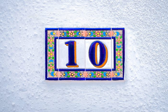 Number 10 / ten, decorative tiles on white surface.