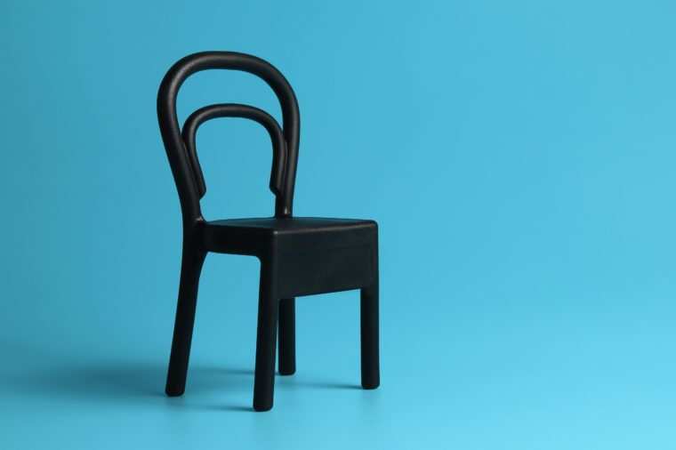 Close up a mini black chair isolated on blue background. Chair person concept.